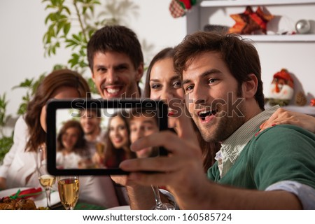 Young friends taking self portrait with digital tablet on Christmas eve.  - stock photo