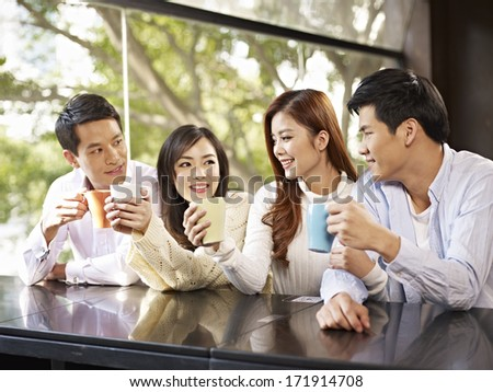 young friends talking and drinking coffee in cafe. - stock photo