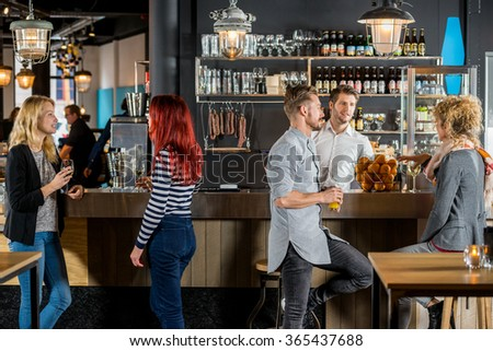 Young friends talking while having their drinks at bar counter - stock photo