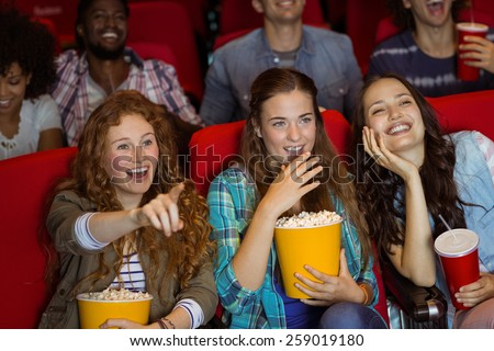 Young friends watching a film at the cinema - stock photo