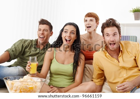 Young friends watching football at home, jittering.? - stock photo