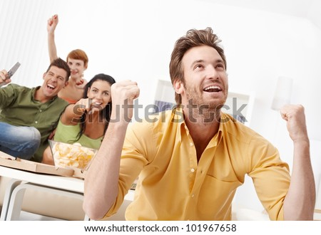 Young friends watching football on tv at home - stock photo