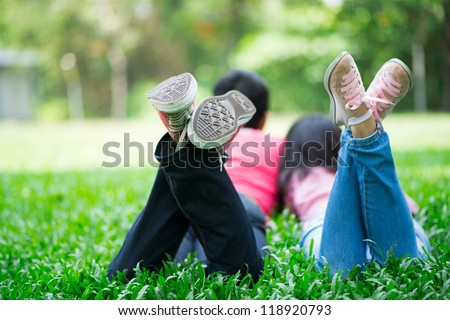 Young friends wearing sneakers lying on the grass in summer