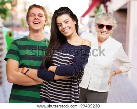 young friends with grandmother smiling at street - stock photo