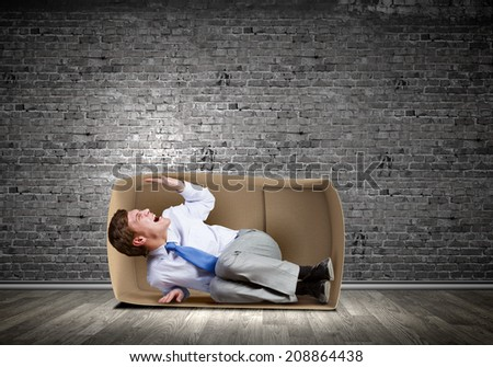 Young frustrated businessman trapped in small carton box