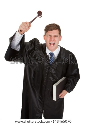 Young Frustrated Male Judge Holding The Gavel And Book Over White Background - stock photo