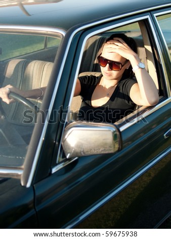 Young frustrated woman driving an old car. Cross processed - retro style image, selective focus. - stock photo