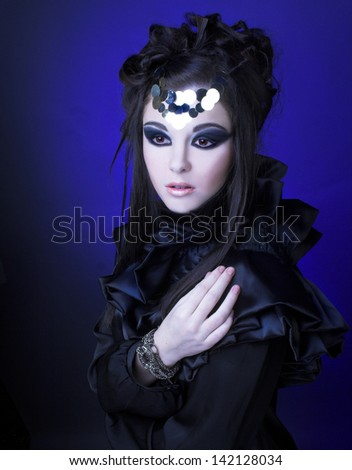 Young ftylish woman in black dress with artistic visage with smokey-eyes - stock photo