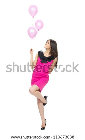 Young full body woman with pink balloons as a present for birthday party smiling and looking at the corner on a white background - stock photo