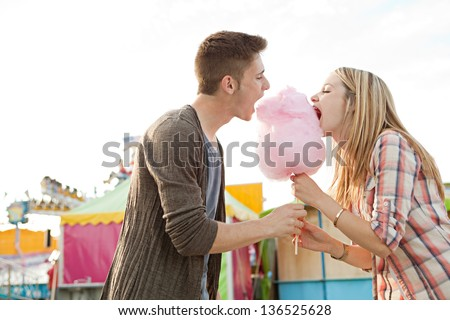 Young fun couple biting into a cotton candy floss sweet at the same time while visiting a colorful amusement park during a sunny day. - stock photo