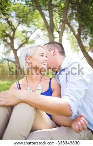 Young funky couple in love and enjoying themselves in a park on a bright sunny summers day.