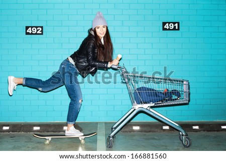 Young funky hipster woman riding skateboard in front pushing shopping cart over blue brick wall. Naughty girl having fun . Indoors, lifestyle - stock photo