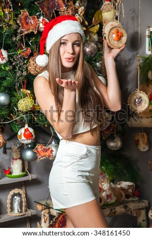 Young funny beautiful fashion model with dark eyes, brown hair and santa hat celebrating new year at home. new year decoration with positive emotion posing and  looking at camera. colored decor. kiss
