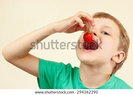 Young funny boy eating a fresh ripe strawberry - stock photo