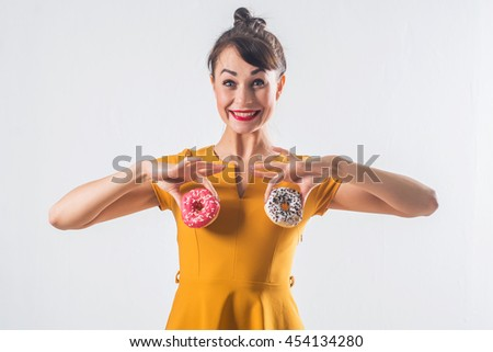 Young funny brunette model with donuts posing studio shot on white background, not isolated. - stock photo