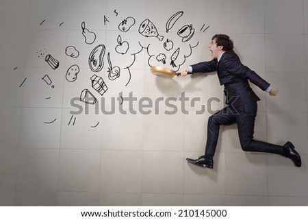 Young funny businessman running with pan in hand - stock photo