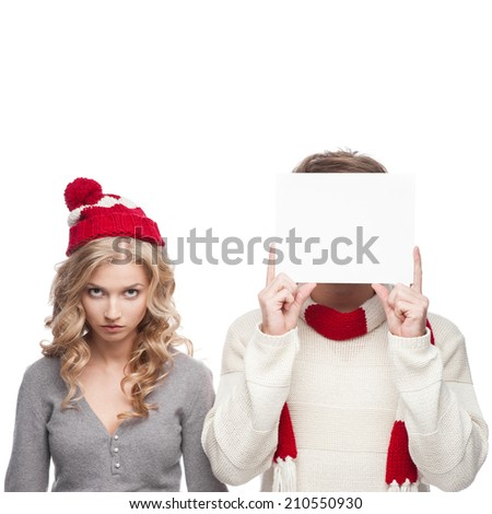 young funny casual caucasian couple holding sign and looking angry at camera - stock photo