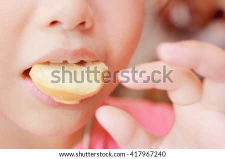 Young funny girl eating cookie and shows delicious expression,yummy cookie.Soft focus  and pink color toned. - stock photo