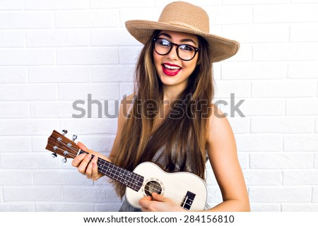 Young funny hipster girl having fun and playing on small ukulele guitar, singing and dancing. wearing vintage glasses and straw hat, joy, positive mood. White urban brick wall background. - stock photo