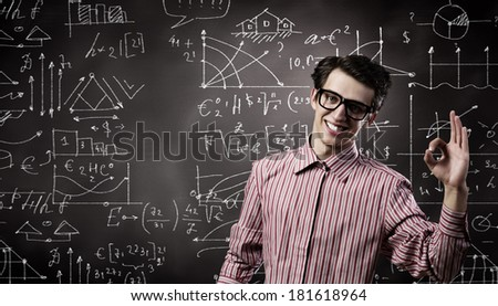 Young funny man in glasses against chalk blackboard - stock photo