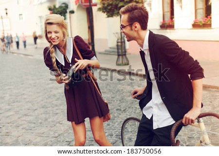 Young funny pretty fashion vintage hipster couple having fun outdoor on the street in summer. Blonde girl with camera make photos of handsome man and laughing