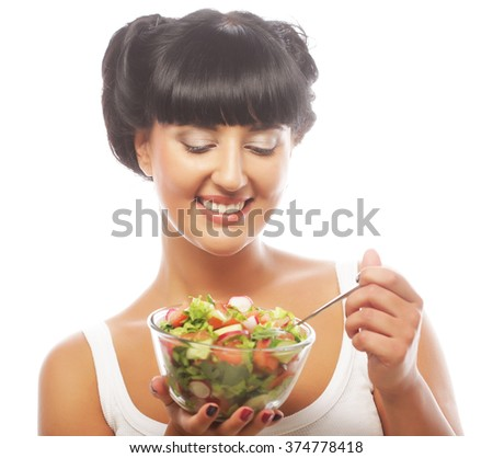 Young funny woman eating salad over white background - stock photo