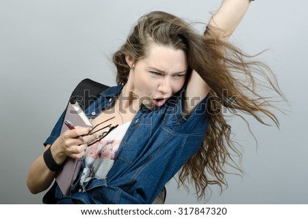 Young funny woman holding book and pulling her hair - stock photo