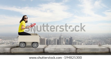 Young funny woman riding in carton box - stock photo