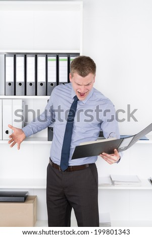 Young furious businessman is looking into an opened file while standing in front of a shelf in the office.