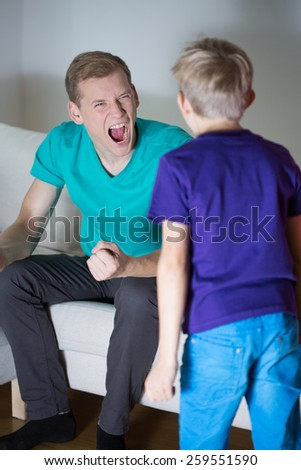 Young furious father yelling at his little son - stock photo