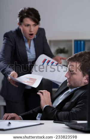 Young furious female boss and her scared young employee - stock photo