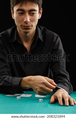 Young gambler man in black shirt sitting at the playing table gets a card from his sleeve isolated on black background. Shallow DOF. Focus on hands. - stock photo
