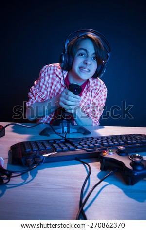 Young gamer like to play video games. In blue light of display kid play computer games online. - stock photo
