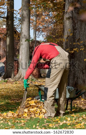 Young gardener during his job in autumn. - stock photo