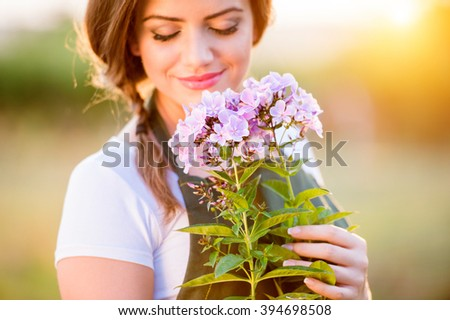 Young gardener in her garden holding flowers, sunny nature