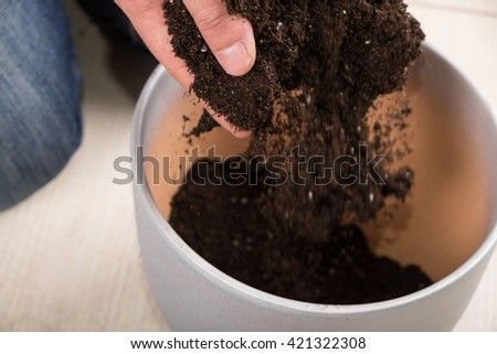 Young gardener pouring bunch of fertile soil in flowerpot while transplanting a plant - stock photo