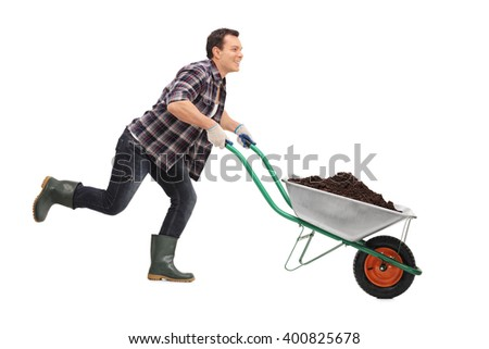 Young gardener pushing a wheelbarrow full of dirt and running isolated on white background - stock photo