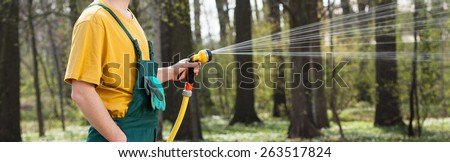 Young gardener watering lawn with garden hose - stock photo