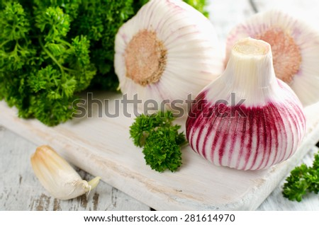 Young garlic and parsley on a white table. Rustic style