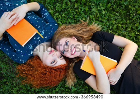 Young gay girlfriends lie on the lawn in the city park. Best friends. BFF - stock photo