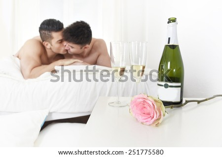 young gay men couple cuddling and kissing lying on bed in bedroom with rose after champagne toast celebrating valentines day in love and passion in homosexual freedom concept  - stock photo