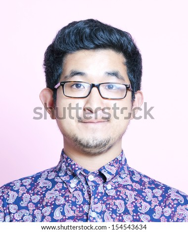 Young Geeky Asian Man in colorful shirt wearing glasses - stock photo