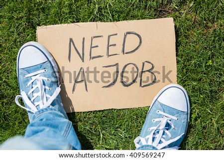 "Young generation employment concept: man with ""need a job"" cardboard"