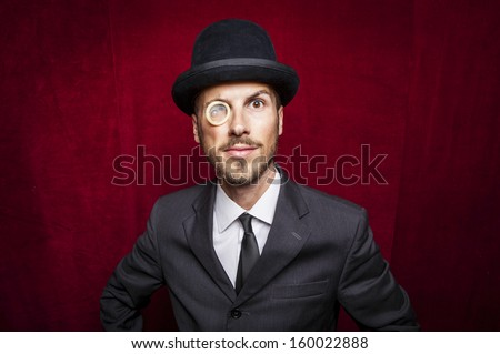 young gentleman with a condom monocle - stock photo