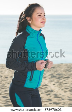 Young germany sporty girl running on beach by ocean in morning