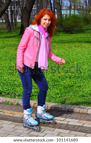 Young ginger girl tying the laces on roller skates in Mariinsky Park in Kiev - stock photo