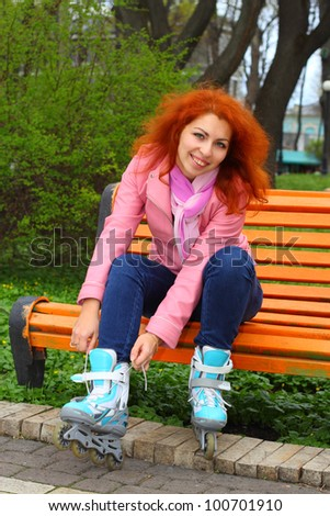Young ginger girl tying the laces on roller skates sitting on the bench in the park - stock photo
