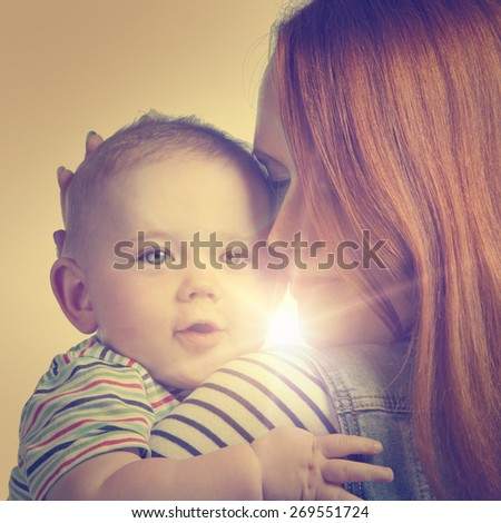 Young ginger woman holds in her arms a little boy - instagram style - stock photo
