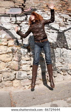 young ginger woman jumping - stock photo