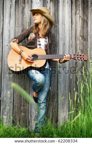 Young girl against a wooden wall playing guitar - stock photo